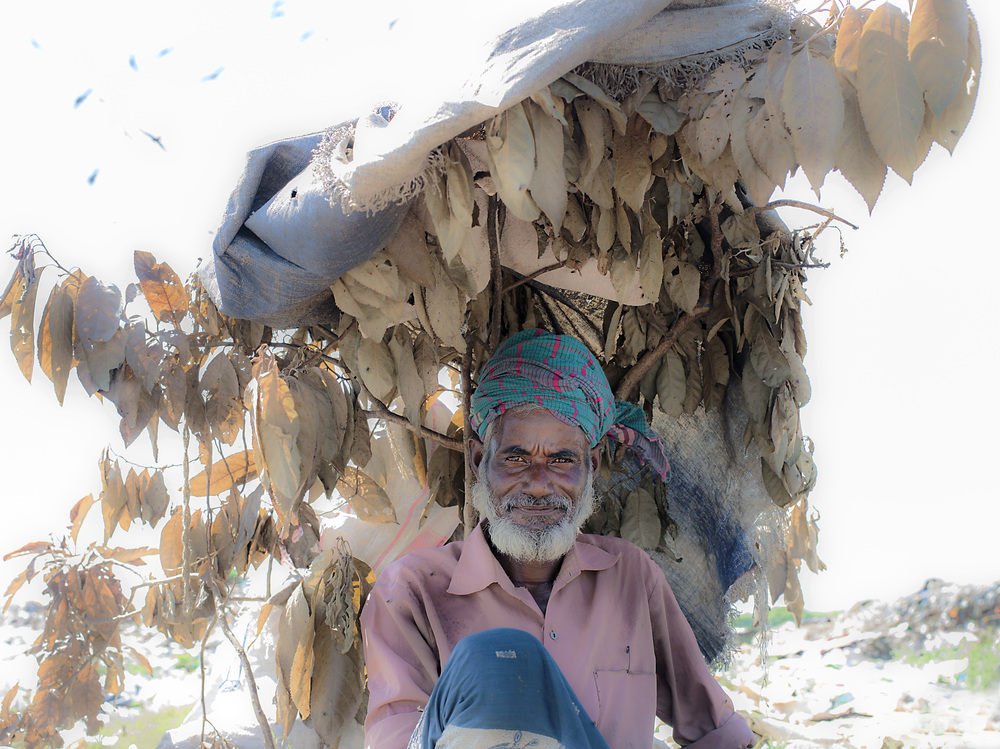 A man relaxing at Parar Chokh Landfill in Sylet, Bangladesh.