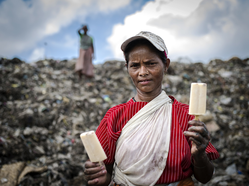A woman holds popsicles to share with her girlfriend at Matuail Landfill in Dhaka, Bangladesh.