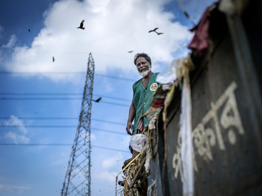 A man drops off trash at Matuail Landfill in Dhaka, Bangladesh.