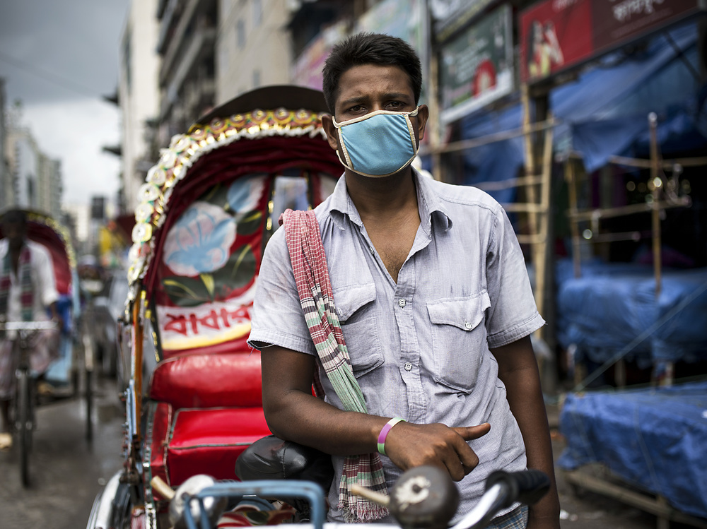A boy working as a driver covers his face from the city's pollution.