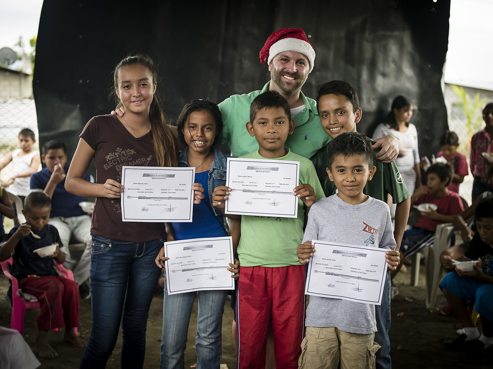 Luis, Maria, Moises and Erick receive English certificates for passing the class. Also pictured in the image is their English teacher, Tupac.
