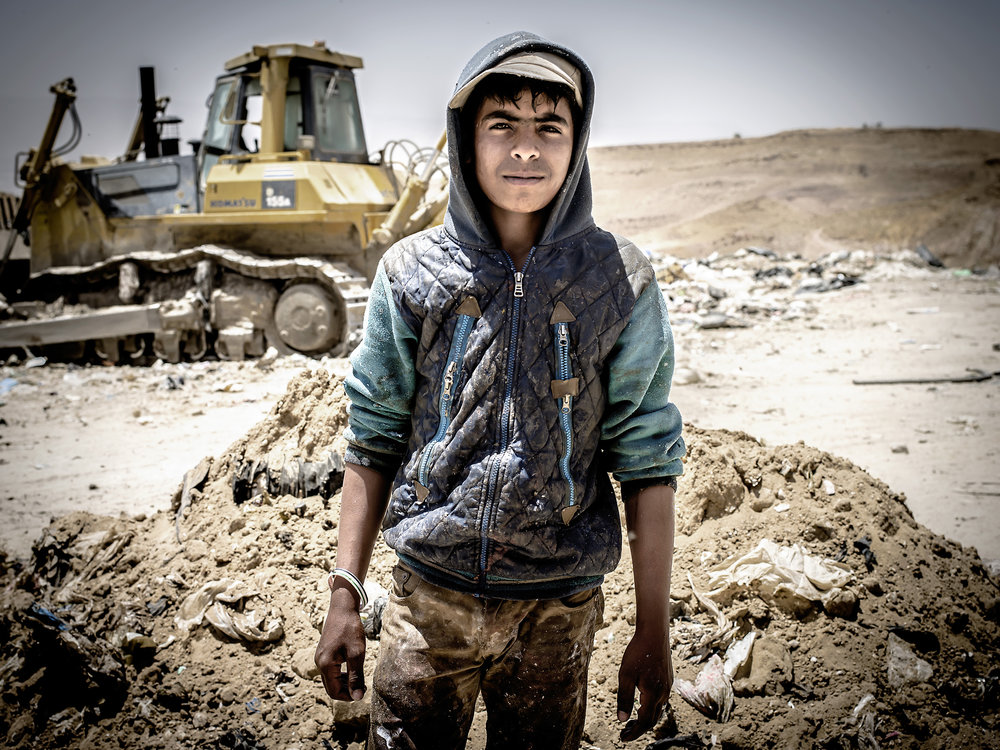 Jihad is 15 years old and stopped going to school to accompany his father to live and work at the dump 15 days at a time.