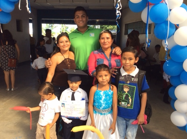 Kevin graduates preschool as his family and ISWA Scholarship Programme supervisor, Kevin Lopez, support his achievement.