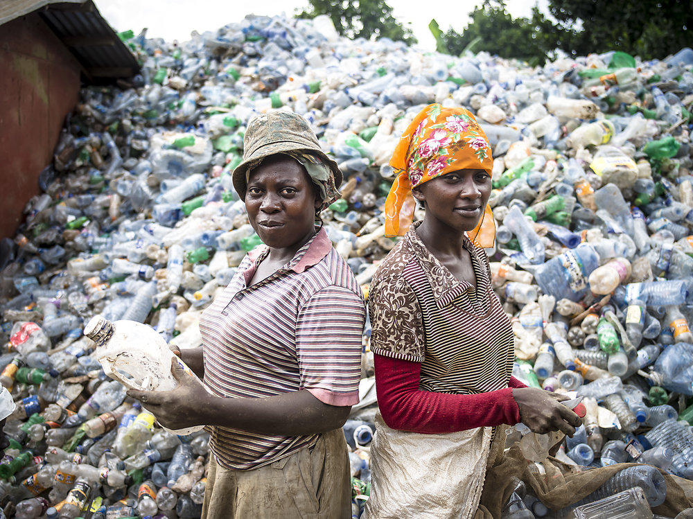 Two women rip off labels from plastic bottles in the Kampala dumpsite.