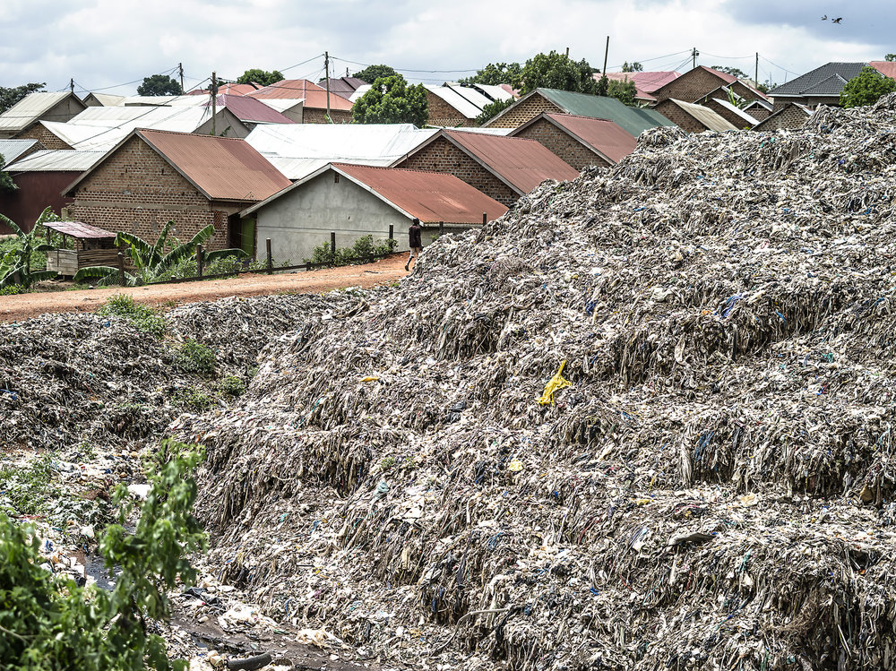 Homes run adjacent to Kampala dumpsite.