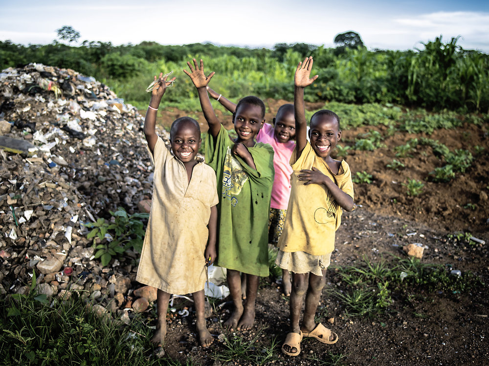 Local children wave hello from a dumpsite where they are looking for materials to sell. Mbarara.