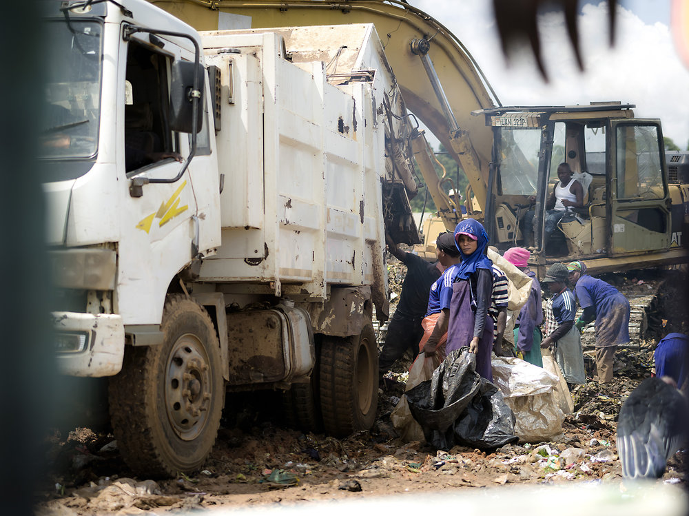 People sorting directly from the garbage truck as they drop of trash. Kampala.