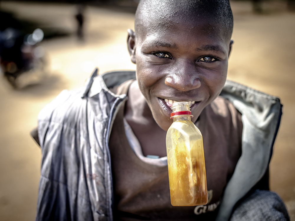 A Boy huffs glue. Glue huffing is common in extreme poor area because it suppresses the appetite. However, it will not also relieve someone of cravings for food when they are hungry, the individual will become high and addicted to the drug at the same time. Mbarara.