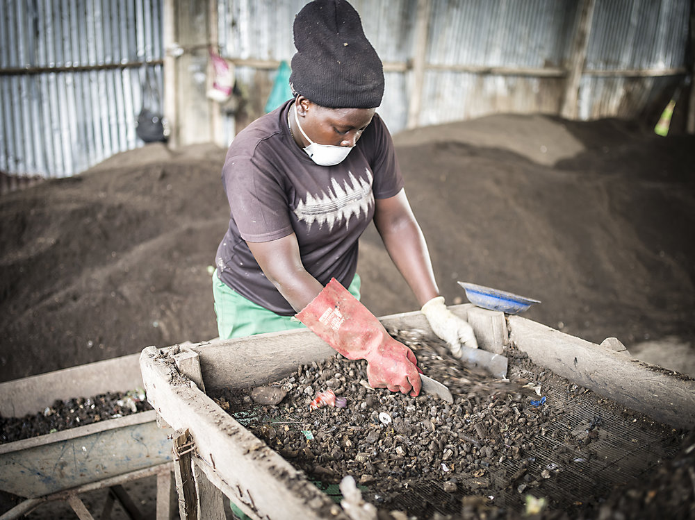 A woman sifts through the dirt to prepare it for gardening. Katikolo.