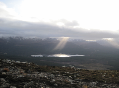 Rays of afternoon sun filter through the clouds to illuminate Loch Morlich