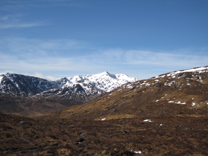 Snow covered Spidean Mhalach rising behind the south Glen Shiel ridge