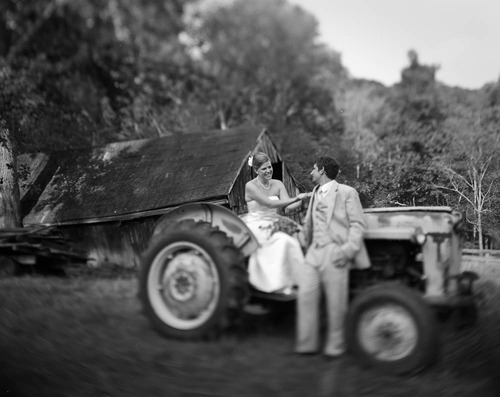 Large format image of a bride and groom on an old tractor