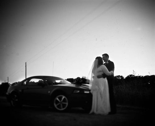 Large format picture of bride and groom outdoors by their car