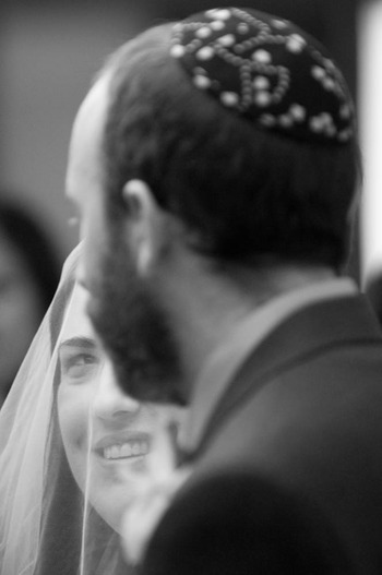 black and white image of a bride looking at her groom