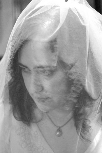 black and white image of a bride covered by her veil