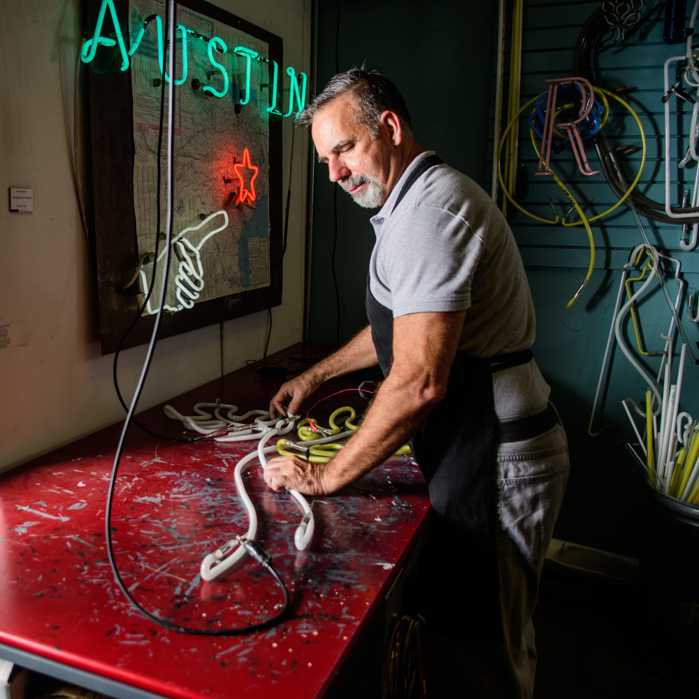 Mark Westphal works on fabricting a neon light at Ion Art in Austin Texas.