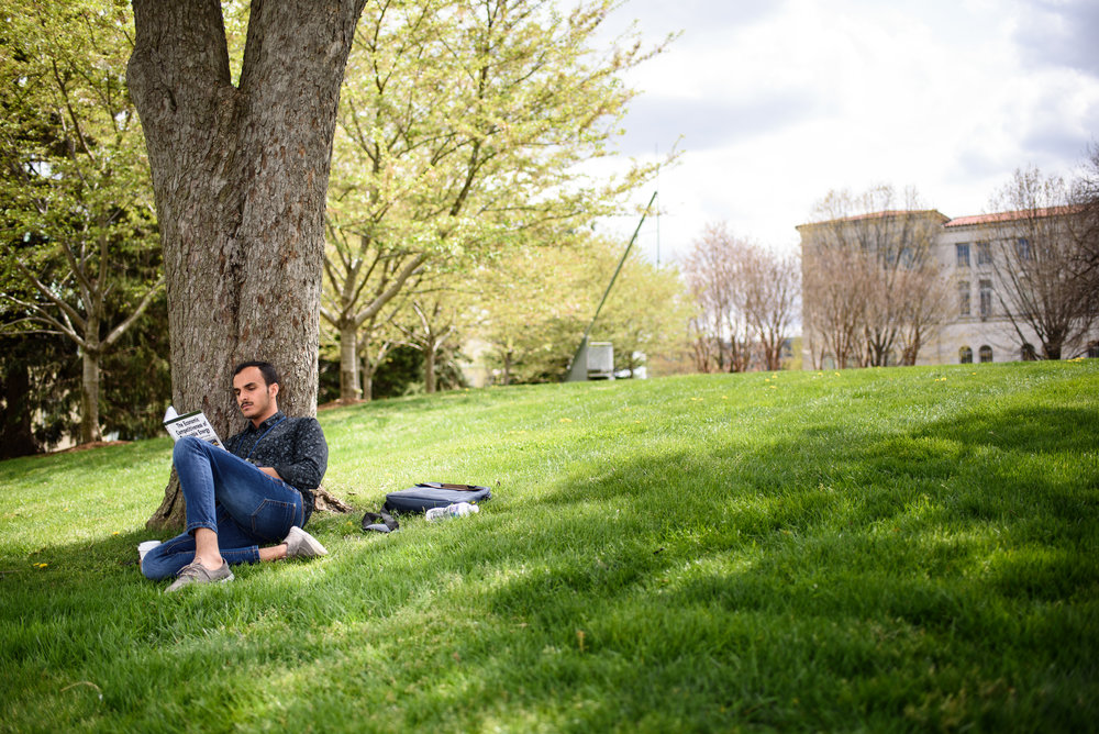 Catholic University studetns reading a book under a tree.