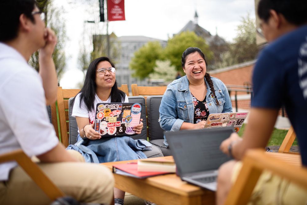 Catholic University students sitting at the benches outside of the Pryzbyla Center in Washington, DC.