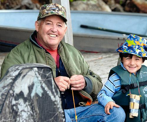 Gary Cobb teaching his grandson Lyle to fish