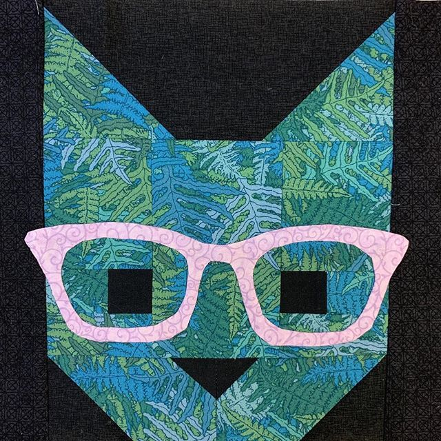 I finally conquered appliqué — just so I could make this quilt pattern. (Image of a blue geometric cat head wearing purple nerd glasses on a black background)  #elizabethhartman #catsinglasses #quilting #applique