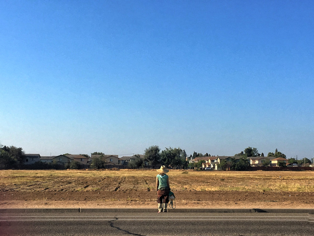 a woman stops to ponder the horizon at a empty plot of land nestled in a subdivision
