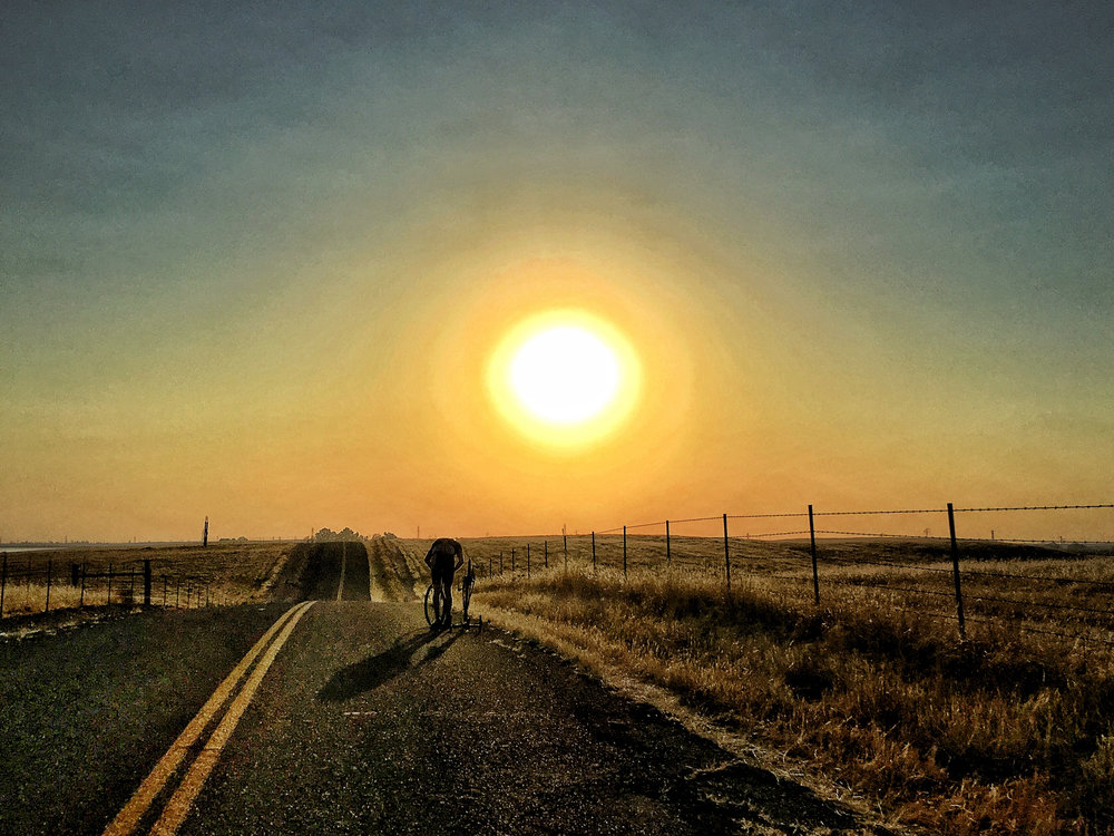 a cyclist stops to change a flat tire under the gaze of the setting summer sun