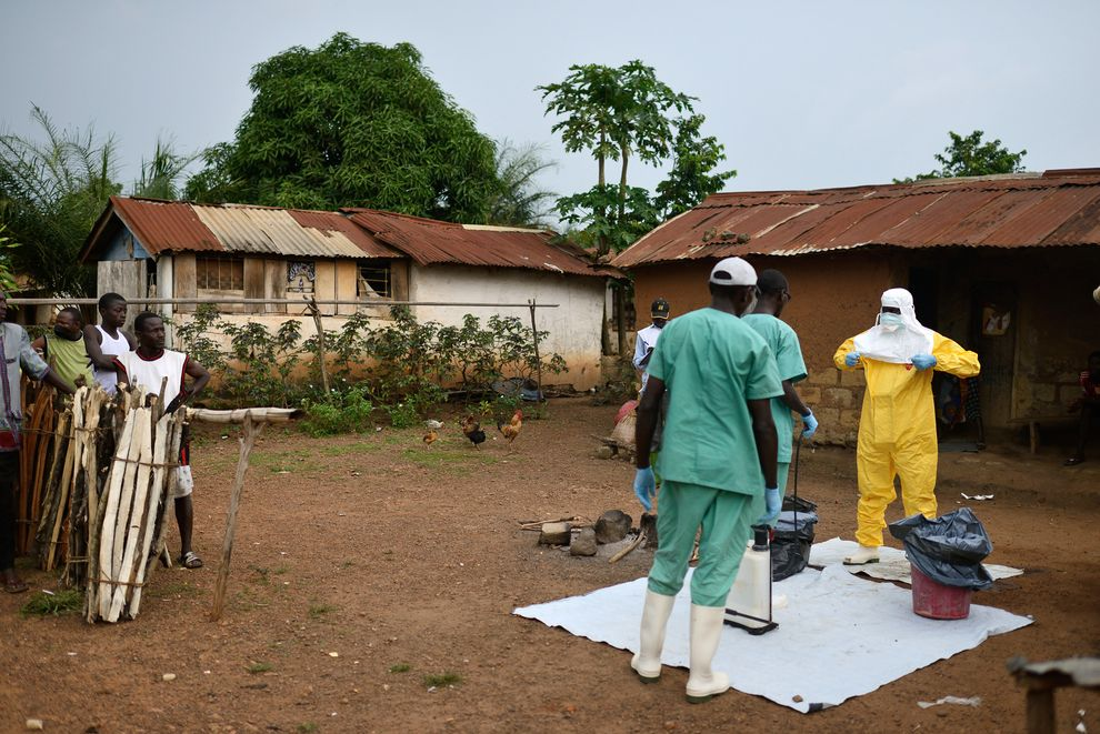 Health workers disinfect after leaving local health clinic; Photo from National Geographic
