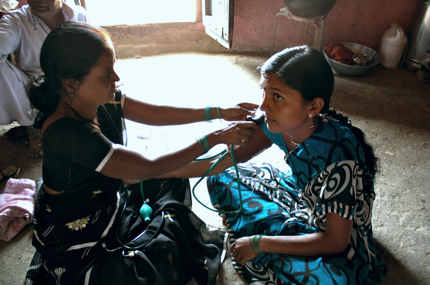 A community health worker takes the pulse of a patient in Rajasthan, India. She is one of a cadre of female health workers that goes door to door, delivering services to communities that otherwise wouldn't have access to quality care.