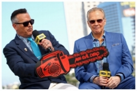 Stars Bruce Campbell and Lee Majors with foam chainsaw