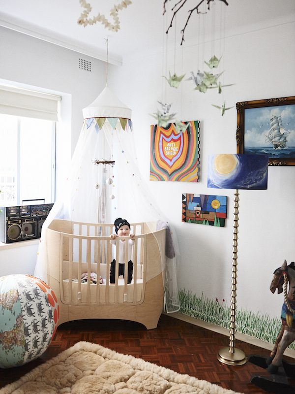 Baby Banjo loves his room!  Leander cot, alpaca rug from Queen Victoria markets, vintage ghetto blaster, anti bad vibe shield by Ozzie Wrong, lampshade by Vanessa Bate, painting by Nick Hernandez, padded exercise ball by Dion Antony artisan.   Photo –  Eve Wilson.  Production – Lucy Feagins/The Design Files.