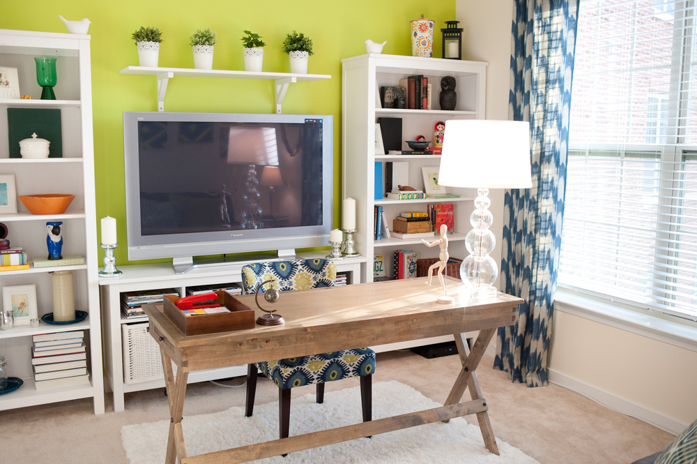 Office design w/ lime accent wall, blue & green ikat chair, blue ikat curtains, ikea white bookshelves, world market rustic desk; designed by Washington DC interior designer Teri Clar on Fortique