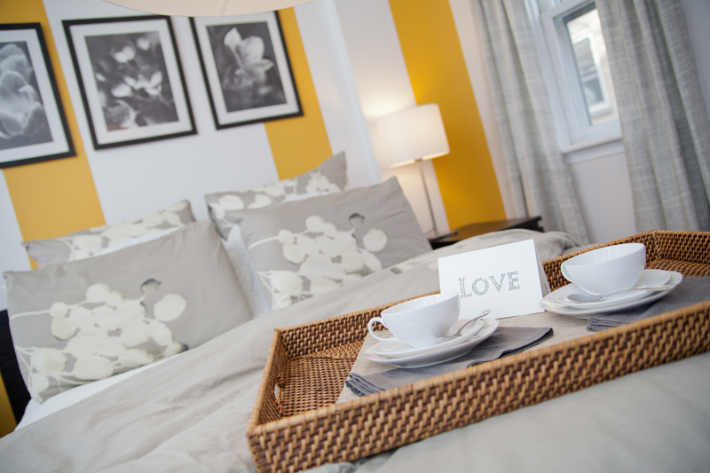 Yellow and white striped accent wall in yellow and gray bedroom; designed by Washington DC interior designer Olios Design on Fortique