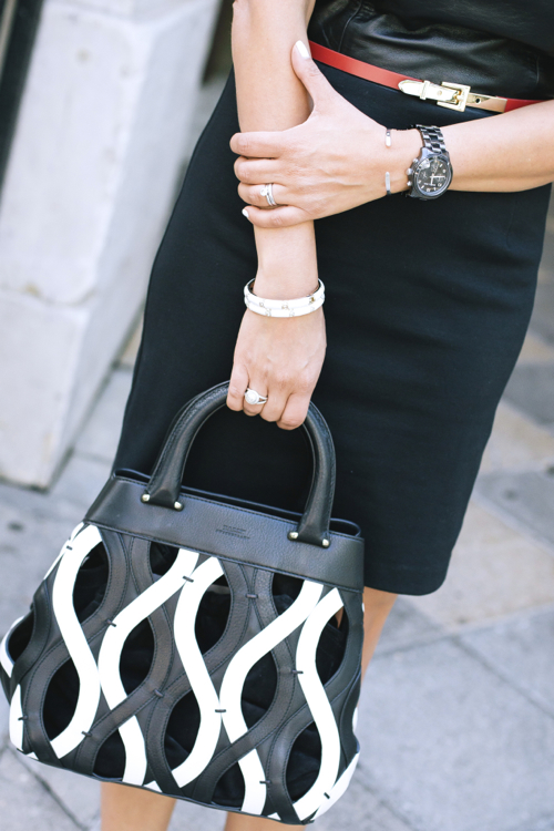 Black dress, skinny orange accent belt, black and white purse styled by top Washington DC stylist Naina Singla on Fortiqu