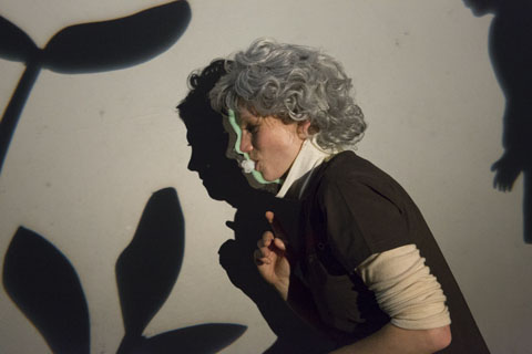 Shows how the puppeteer create a shadow image of on old woman with a profile mask held by a mouth piece.
