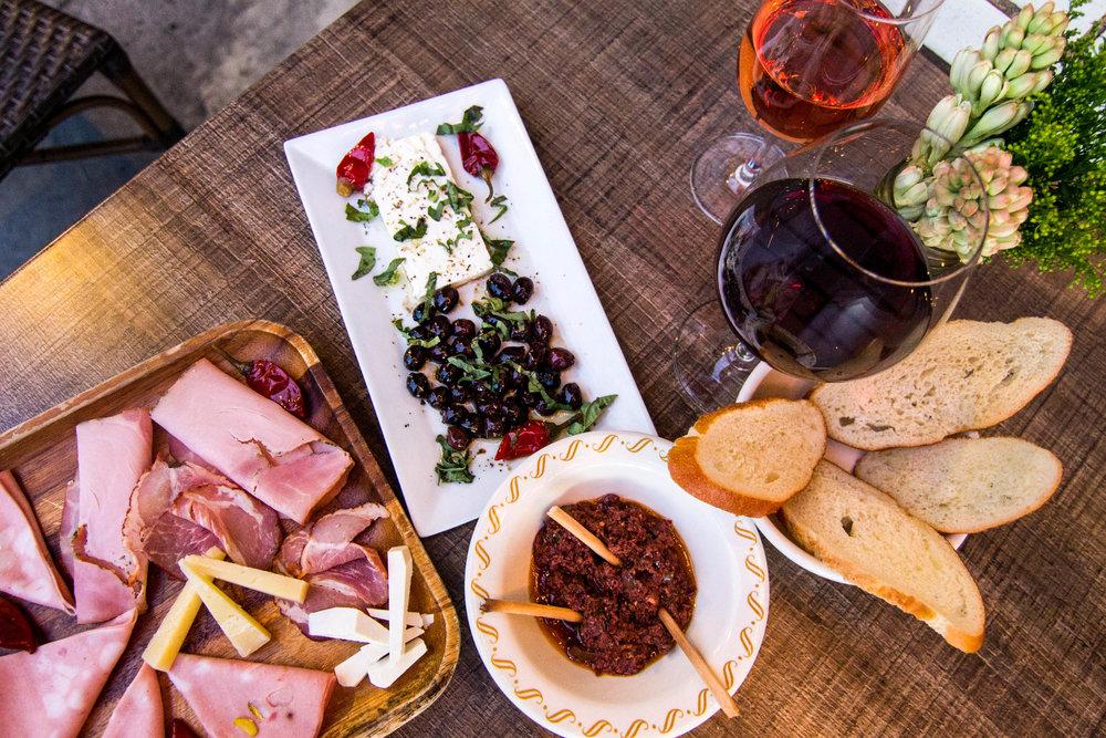 Plato di legno with wine and a basket of bread outdoors