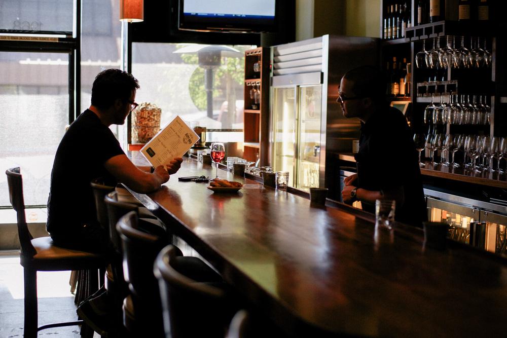 Man perusing menu inside a wine bar
