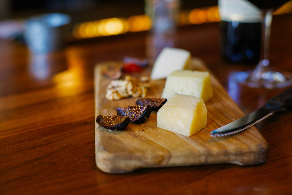 Cheese board with a glass of red wine inside a wine bar