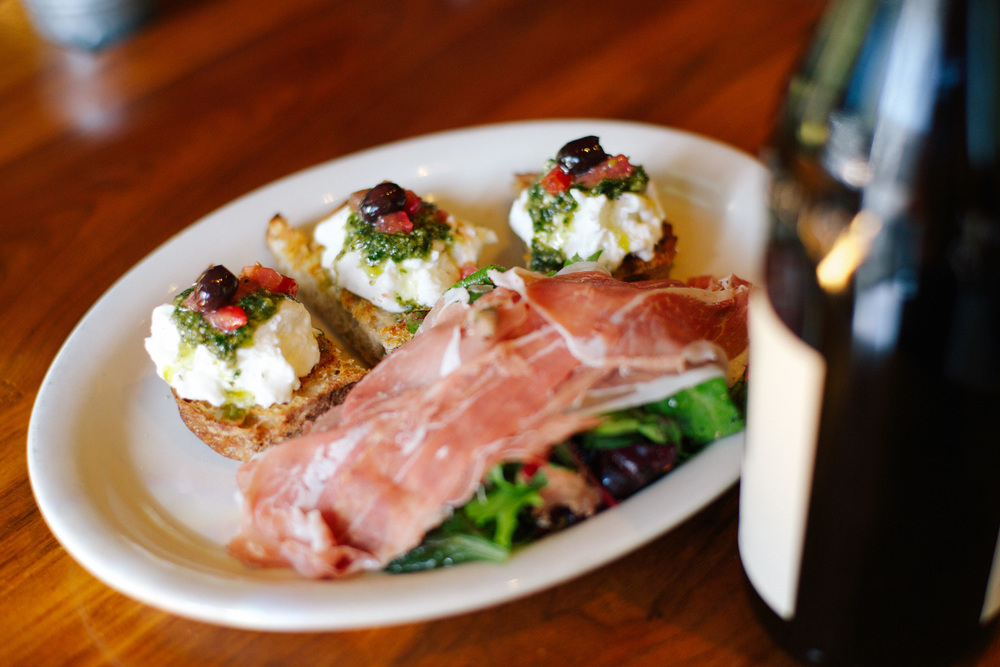 Plate of brushetta with a bottle of wine