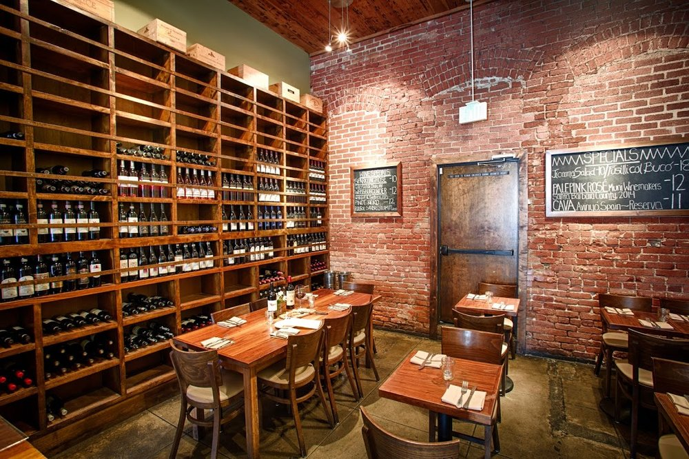 Inside of a wine bar showing restaurant tables and a large wine rack filled with wine bottles