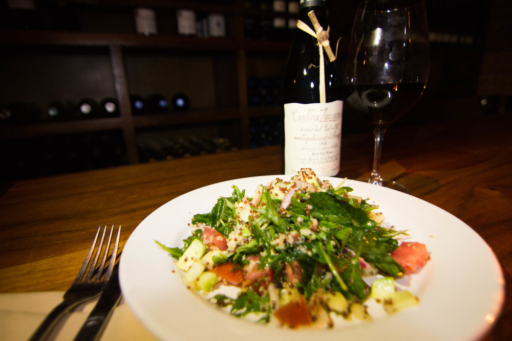 Green salad paired with wine inside a wine bar