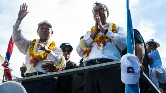 Sam Rainsy, right, and Kem Sokha - the leaders of the Cambodian National Rescue Party (CNRP) greet crowds as they roll through Phnom Penh atop a customized tuk-tuk.