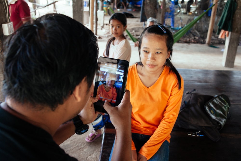 Phearom, an Alongsiders Cambodia staff, takes a photo of Matha while Esara watches.