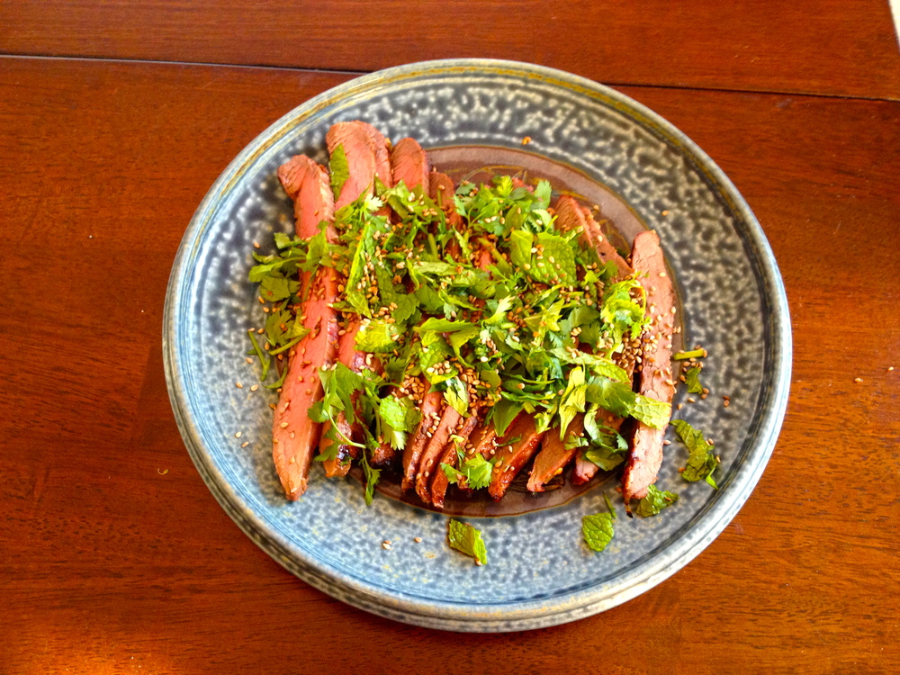 Flank steak topped with cilantro, mint, & sesame seeds