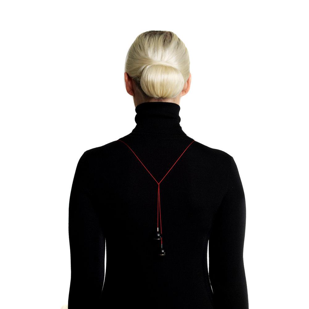Her ser du hvordan de røde silkesnorene balanserer vekten av fronten og de sorte onyxkulene som hviler i sølvskåler.