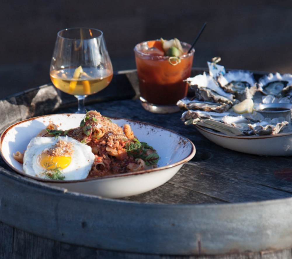 Lamb Bolognese, local oysters and drinks on the dock at Westward, a nautical-themed top Seattle restaurant serving fresh Pacific Northwest-style Mediterranean Fare.
