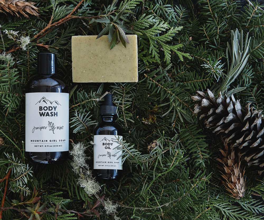 Juniper and mint body wash, oil and soap shown on a forest floor of hemlock, cedar, leaves, pine cones, moss and dirt.