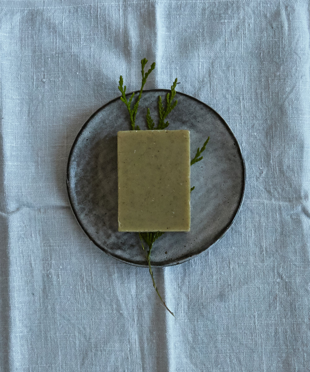 Juniper and mint soap bar sitting over a piece of cedar.
