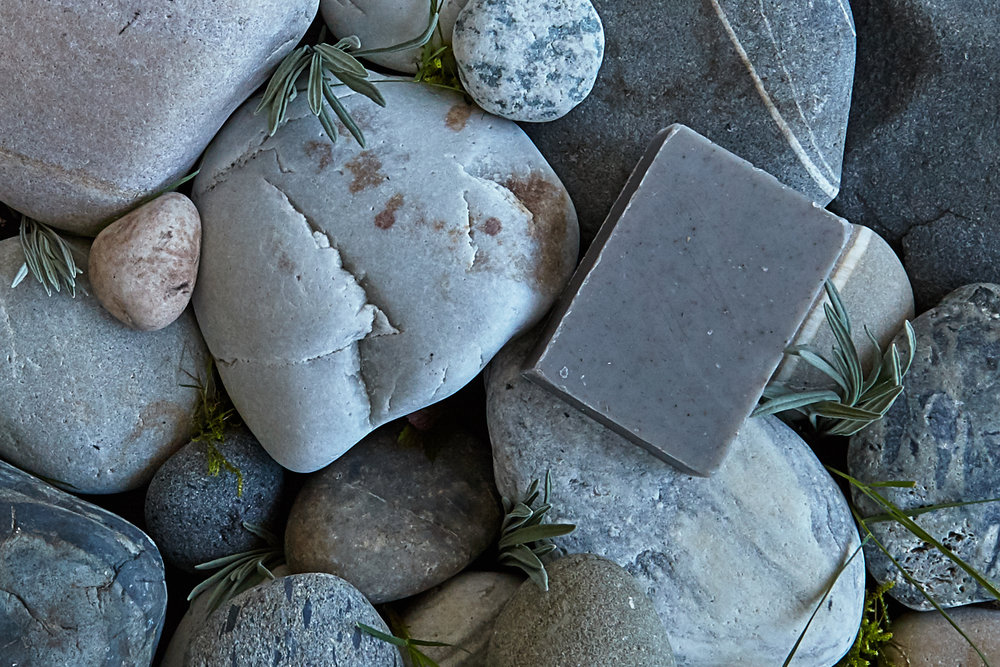 Desert Lavender bar shown on stones collected from Orcas Island, with lavendar leaf poking out.
