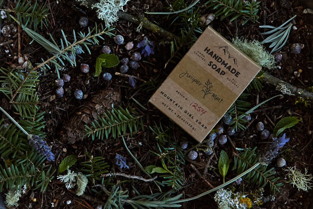Juniper and mint soap bar shown in packaging on a forest floor consisting of dirt, hemlock, moss, lichen, pine cones, juniper berries, mint leaves, and lavender.