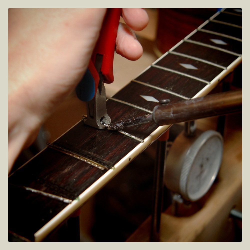 Refret: Heating frets while removing helps minimise fingerboard chipping